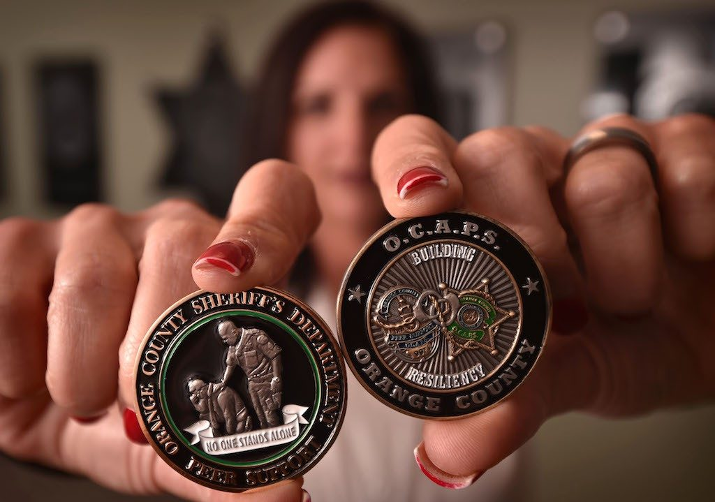 "Heather Williams, regional peer support coordinator for the Orange County Sheriff's Department, holds the Orange County Sheriff's Challenge Coin, left, for peer support particpants with the theme ""No One Stands Alone."" On the right is the Orange County Association Of Peer Supporters, or OCAPS, coin. The graphic on the right represents, according to Williams, ""Law Enforcement of Orange County, intertwined and working together in the event that a department needs mutual aid or support in the aftermath of a critical incident."" Photo by Steven Georges/Behind the Badge OC"